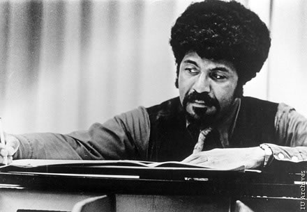 David Baker looking at music on a piano.