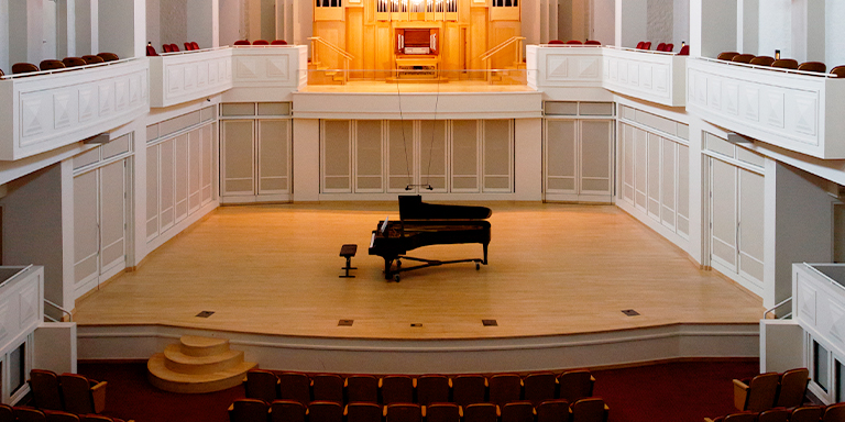 Image from inside Auer Hall, the stage sits above the center audience and is surrounded by balcony seating. The Seward organ is visible starting on the second floor.