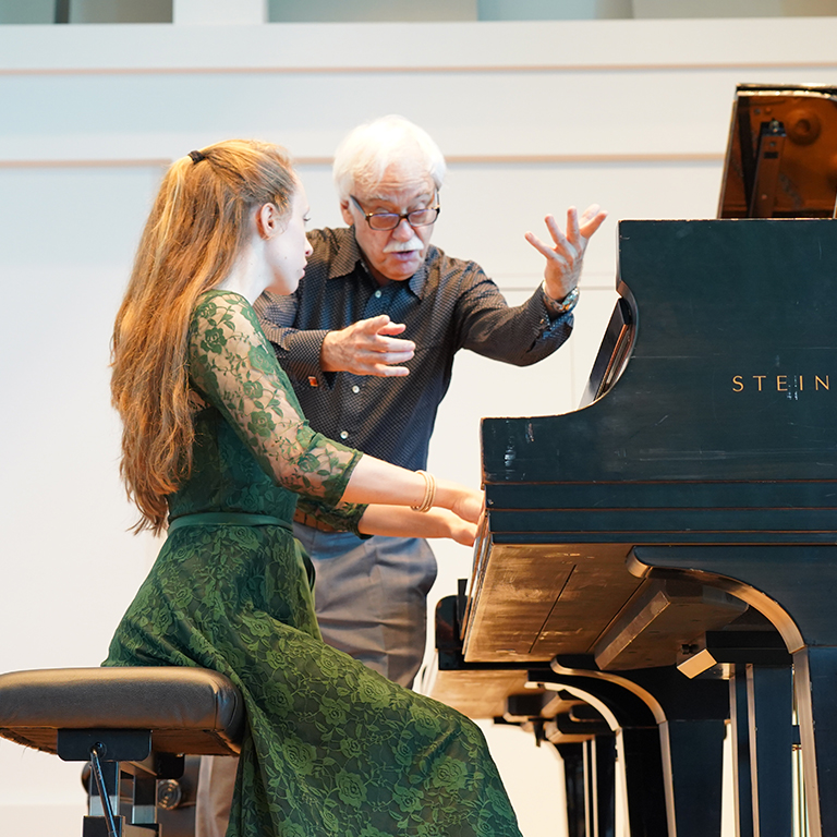 Edward Auer instructing a student at the piano.